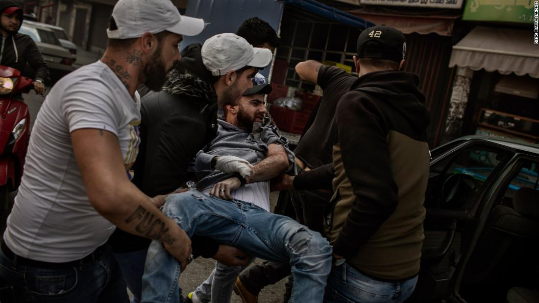 A protester is carried after being wounded by a rubber bullet.