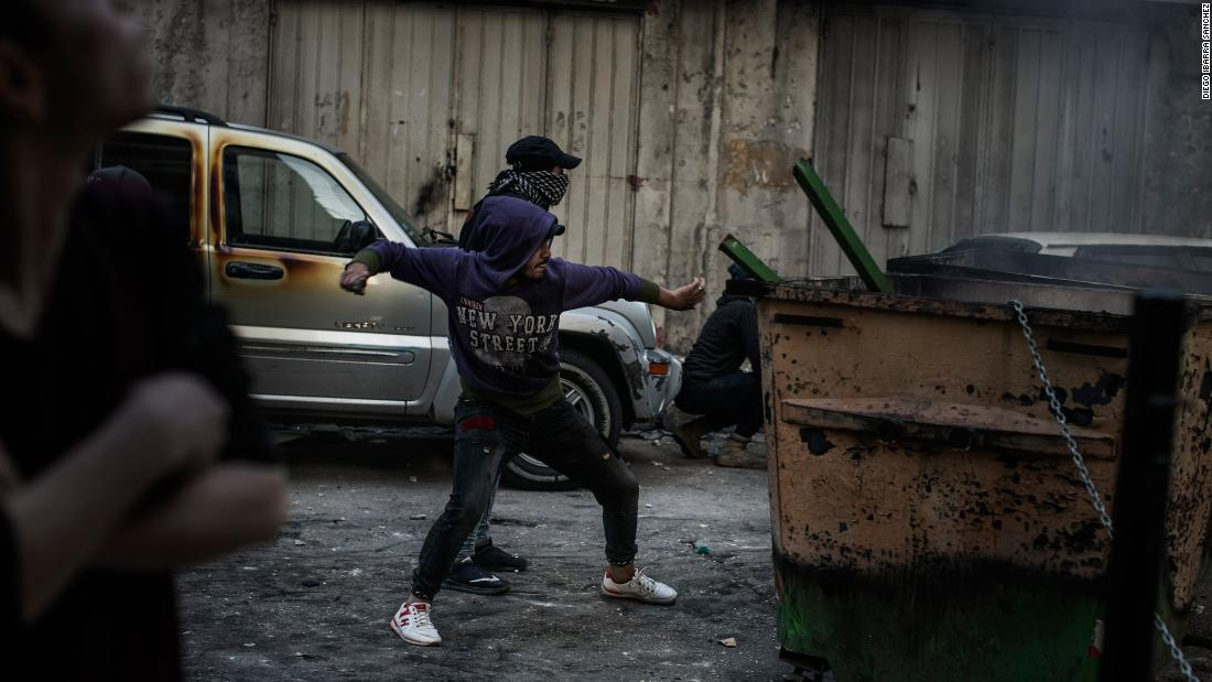 "A protester throws a rock at soldiers on Tuesday. Demonstrations in Lebanon <a href=""http://www.cnn.com/2019/10/29/world/gallery/lebanon-protests-political-crisis-intl/index.html"" target=""_blank"">first began in October,</a> when the government proposed a tax on WhatsApp calls, along with other austerity measures. Hundreds of thousands of people took to the streets in a bubbling-over of fury at political elites."