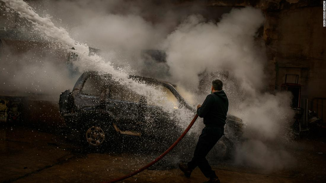A member of the Lebanese Civil Defense extinguishes a police car that was set on fire by protesters in Tripoli.