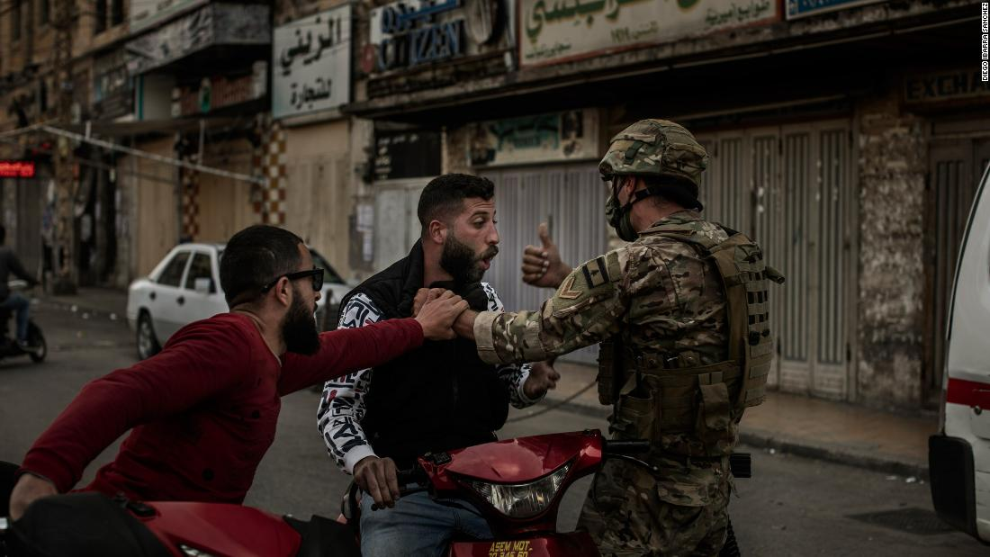 A soldier stops a man on a motorcycle during Tuesday's clashes.
