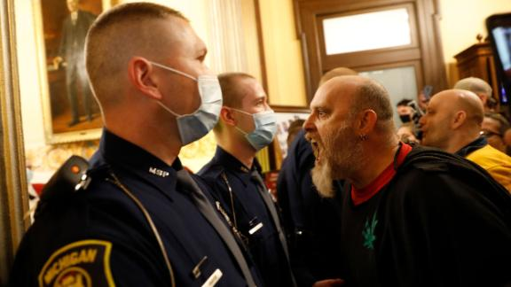 Protesters try to enter the Michigan House of Representative chamber and are being kept out by the Michigan State Police after the American Patriot Rally organized by Michigan United for Liberty protest for the reopening of businesses on the steps of the Michigan State Capitol in Lansing, Michigan on April 30, 2020.