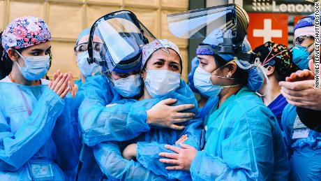 Medical workers outside Lenox Health Greenwich Village on Thursday as people applaud medical staff and essential workers on the front lines of the coronavirus pandemic.
