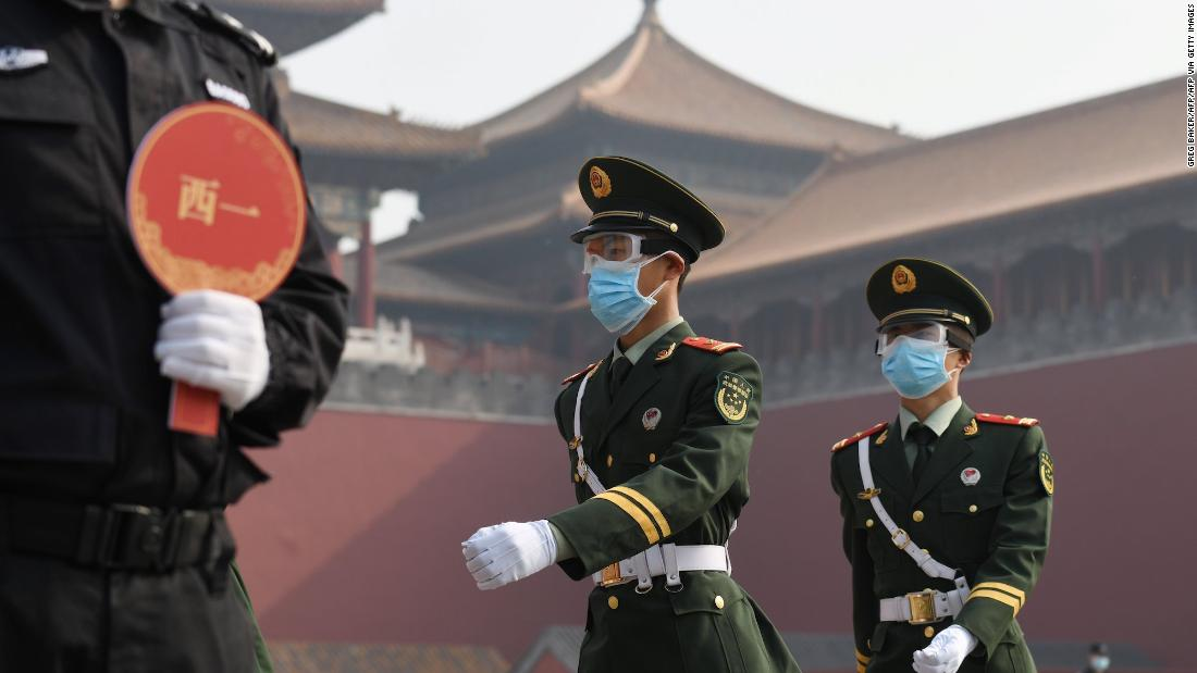 Paramilitary police officers wear face masks and goggles amid concerns of the COVID-19 coronavirus as they march outside the Forbidden City, the former palace of China's emperors, in Beijing on May 1, 2020. - China's Forbidden City reopened on May 1, three months after it closed due to the coronavirus crisis -- the latest signal that the country has brought the disease under control. (Photo by GREG BAKER / AFP) (Photo by GREG BAKER/AFP via Getty Images)