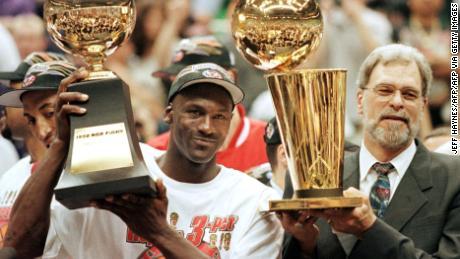 Jordan, seen here with Phil Jackson, raises his NBA Finals MVP trophy.
