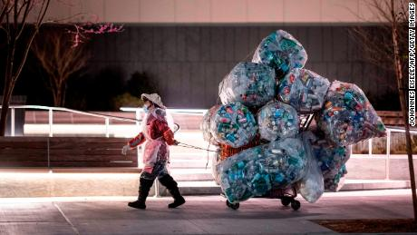 A woman wearing a face mask and a plastic bag pulls a cart loaded with bags of recyclables through the streets of Lower Manhattan in April.