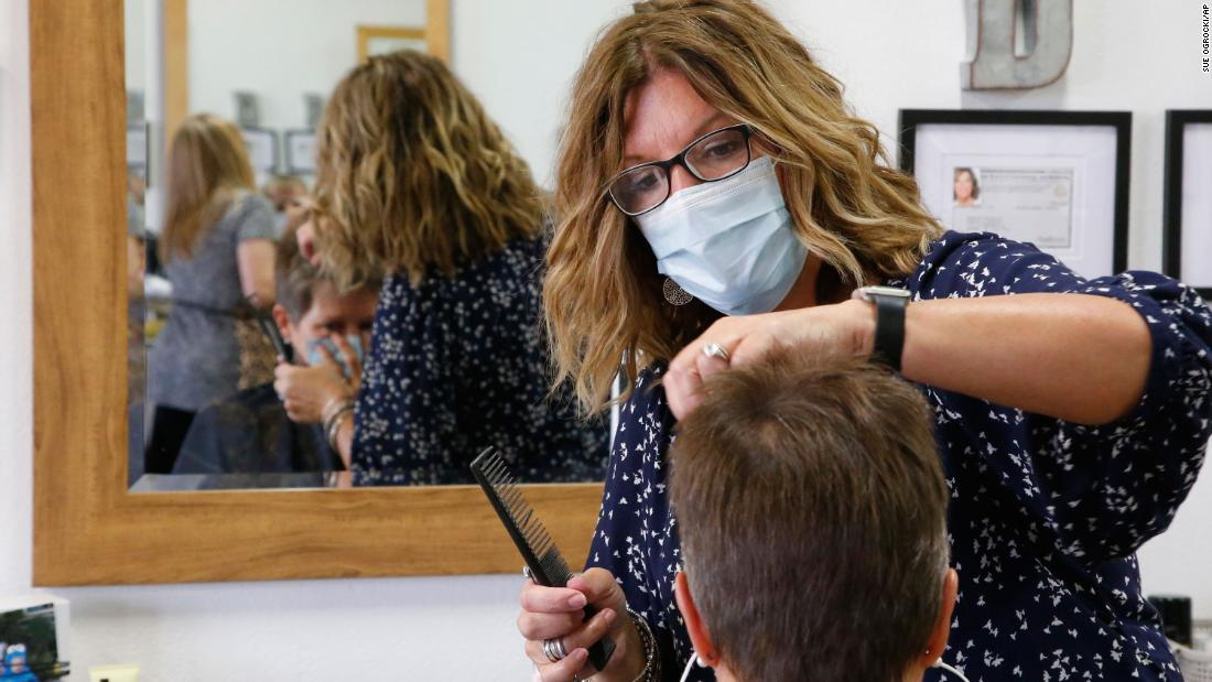 Denise Gravitt, top, cuts the hair of client Lisa Murray, bottom, at her salon, Beehive Salon, Friday, May 1, 2020, in Edmond, Okla., the first day hair salons have been allowed to reopen in Edmond following shutdowns due to coronavirus concerns.