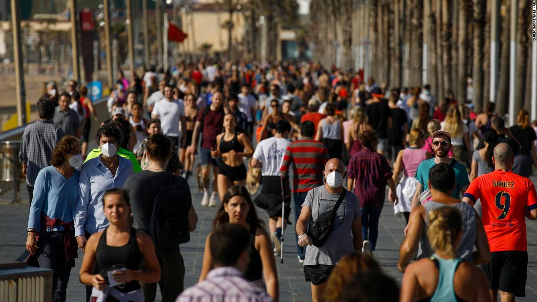 People exercise on a seafront promenade in this photo taken with a telephoto lens in Barcelona, Spain, Saturday, May 2, 2020. Spaniards have filled the streets of the country to do exercise for the first time after seven weeks of confinement in their homes to fight the coronavirus pandemic. People ran, walked, or rode bicycles under a brilliant sunny sky in Barcelona on Saturday, where many flocked to the maritime promenade to get as close as possible to the still off-limits beach. (AP Photo/Emilio Morenatti)