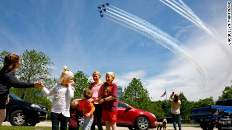 The Ferry family from Chantilly, Virginia, is surprised by a second flyover by the Blue Angels and Thunderbirds seen near the Marine Corps War Memorial in Arlington, Virginia, on Saturday.