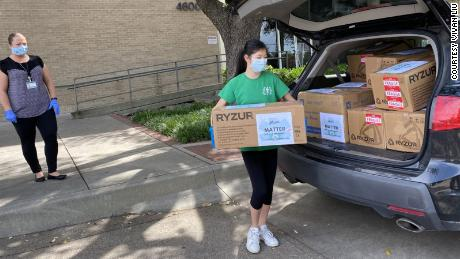 Xu unloading boxes of masks she paid for with funds raised through an online campaign.
