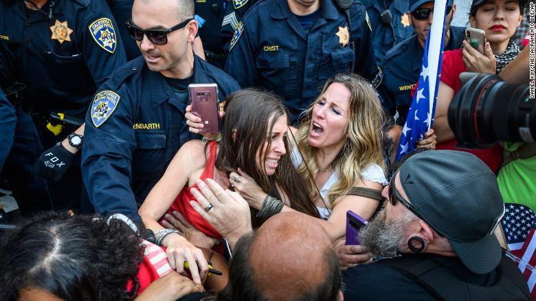 Heidi Munoz Gleisner, center left, is removed from a protest against California's stay-at-home order.