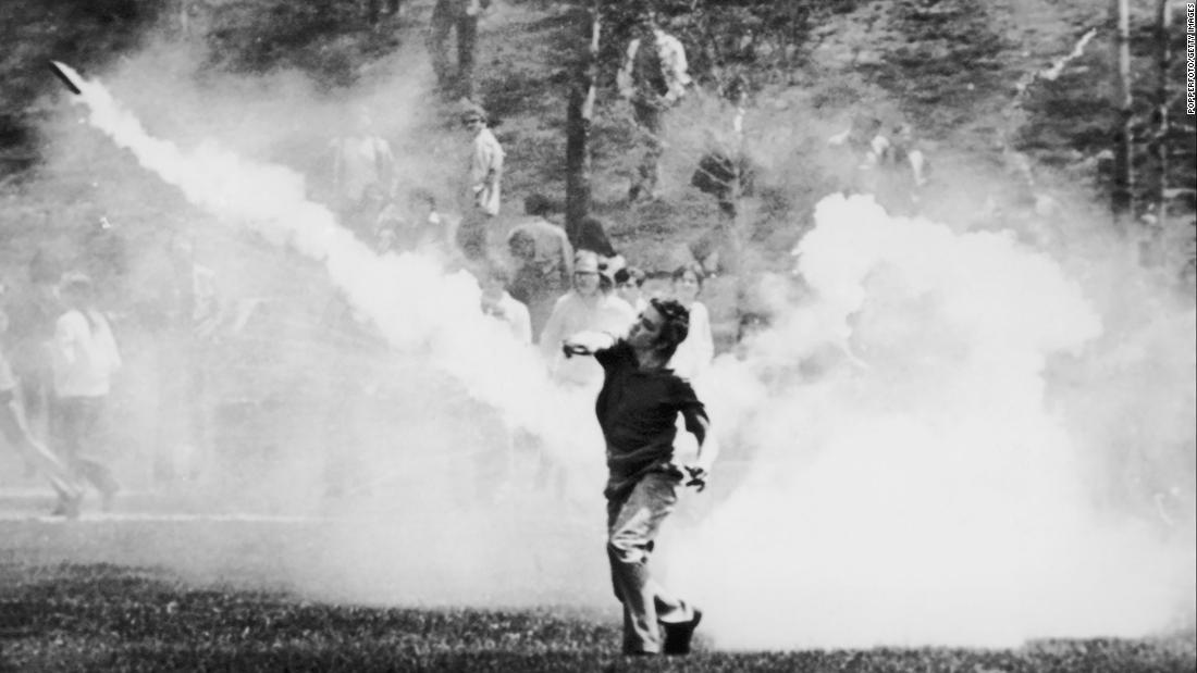 A student throws a tear-gas canister back at guardsmen during clashes on May 4, 1970. After several standoffs, the troops headed back up a hill in the direction of the ROTC building. As they reached the top, they turned toward the demonstrators and opened fire.
