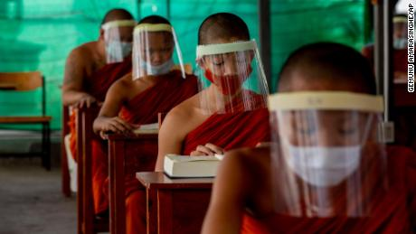 Novice Buddhist monks with protective masks and face shields, seated maintaining social distancing participate in a religious class at Molilokayaram Educational Institute in Bangkok, Thailand, Wednesday, April 15, 2020. All schools in Thailand were closed earlier than the scheduled school break due to the COVID-19 outbreak but about 200 novice monks remain in the monastic school due to travel restrictions and lockdowns implemented in provinces in Thailand. (AP Photo/Gemunu Amarasinghe)