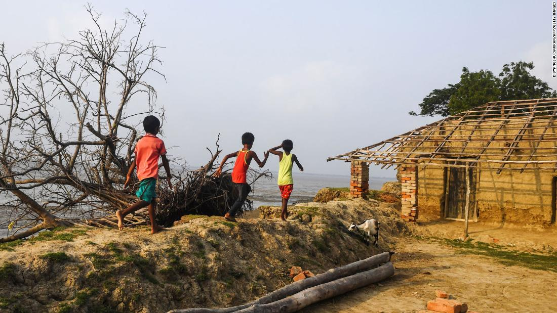 TOPSHOT - In this photo taken on May 18, 2019, Indian children play on the coast affected by erosion on the Ghoramara island around 110 km south of Kolkata, ahead of the 7th and final phase of India's general election. - Residents on Ghoramara fear that the votes they cast on May 19 in India's election may be the last before their island sinks into the Bay of Bengal -- a victim of climate change's growing toll. (Photo by DIBYANGSHU SARKAR / AFP) / To go with story 'INDIA-VOTING-ELECTION-ENVIRONMENT-CLIMATE' by Bhuvan Bagga        (Photo credit should read DIBYANGSHU SARKAR/AFP via Getty Images)
