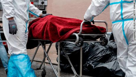 TOPSHOT - People in Hazmat suits transport a deceased body on a stretcher outside a funeral home in Brooklyn on April 30, 2020 in New York City. - Dozens of bodies have been discovered in unrefrigerated overflow trucks outside the Andrew T. Cleckley Funeral Home, following a complaint of a foul odor. (Photo by Johannes EISELE / AFP) (Photo by JOHANNES EISELE/AFP via Getty Images)