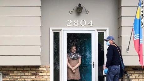 Emerson greets her mail carrier, Doug Scott, at her front door.