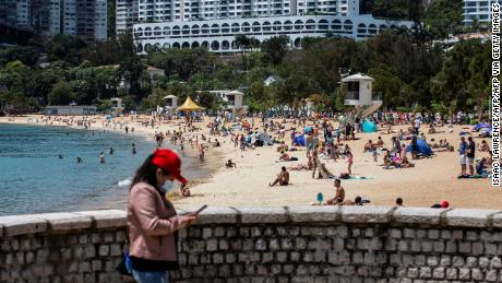 A woman (L) uses her smart phone while people (C) use the beach in Hong Kong on April 13, 2020. (Photo by ISAAC LAWRENCE / AFP) (Photo by ISAAC LAWRENCE/AFP via Getty Images)
