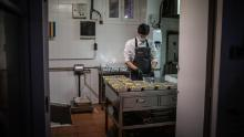 A cook works in Barcelona, Spain on April 16 after his restaurant's kitchen was converted to prepare food for health personnel and vulnerable people.