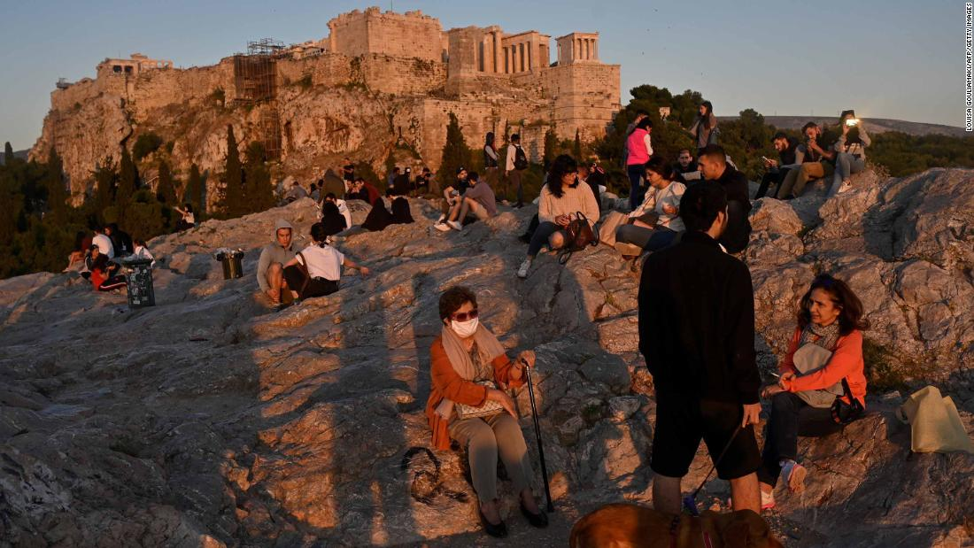 People enjoy a sunset in the Aeropagus hill overlooking the Ancient Acropolis in Athens on May 5, 2020 as Greece gradually eases its lockdown against the spread of the COVID-19, the novel coronavirus, lifting up most of the restrictions on citizens' movement. (Photo by Louisa GOULIAMAKI / AFP) (Photo by LOUISA GOULIAMAKI/AFP via Getty Images)
