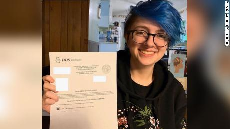 Willa Pevey, 17, holding up a receipt of approval for her new drivers license that she applied for online without taking a road test.