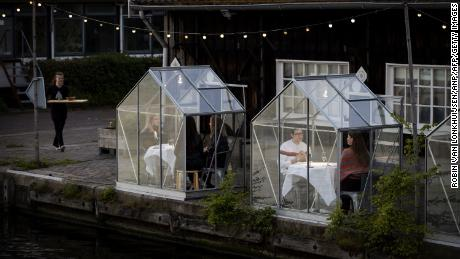 People have dinner in a so-called quarantine greenhouses in Amsterdam, on May 5, 2020 as the country fights against the spread of the COVID-19, the novel coronavirus.