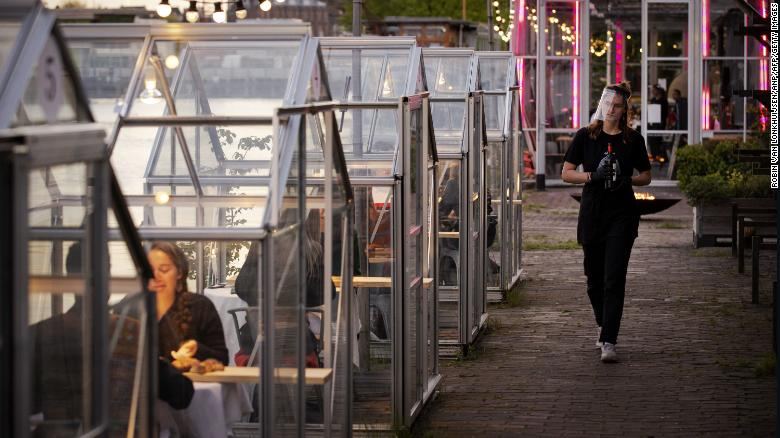 A waitress wearing a protective face shield arrives to serve wine to friends having dinner in a so-called quarantine greenhouses in Amsterdam, on May 5, 2020 as the country fights against the spread of the COVID-19, the novel coronavirus.