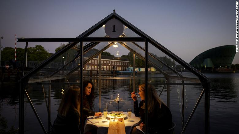 A group of friend have dinner in a so-called quarantine greenhouses in Amsterdam, on May 5, 2020 as the country fights against the spread of the COVID-19, the novel coronavirus.