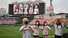 Cheerleaders pose in front of a big screen displaying baseball fans cheering from their homes during the opening game of South Korea's new baseball season between the SK Wyverns and Hanwha Eagles at Munhak Baseball Stadium in Incheon on Tuesday.