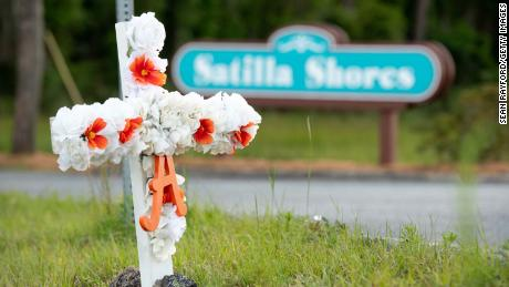 """A cross with flowers and a letter """"A"""" sits at the entrance to the Satilla Shores neighborhood where Ahmaud Arbery was shot and killed in Brunswick, Georgia."""