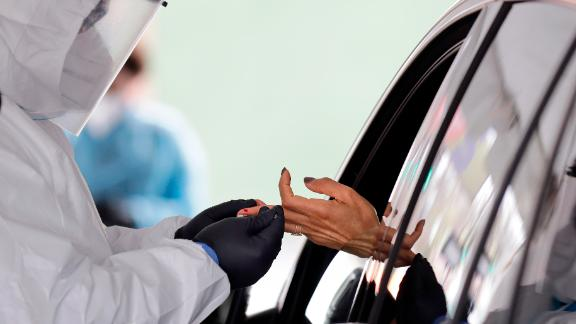 FILE - In this Tuesday, April 14, 2020 file photo, a woman holds her hand out to have blood collected for a 15-minute test for COVID-19 coronavirus antibodies at a drive thru site in Hempstead, N.Y. Antibodies are the markers of infections that someone already had. (AP Photo/Seth Wenig)