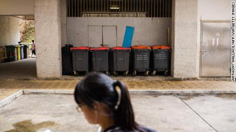 A girl walks past huge garbage cans on the housing estate where the patient from rat hepatitis in 2018 lived. A rat infection was found in the estate.