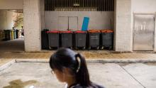 A girl walks past large trash bins at housing estate where the 2018 rat hepatitis patient lived. A rat infestation was found in the estate.