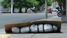 An abandoned corpse wrapped in plastic and covered with cardboard lies on a sidewalk in Guayaquil, Ecuador, on April 6.