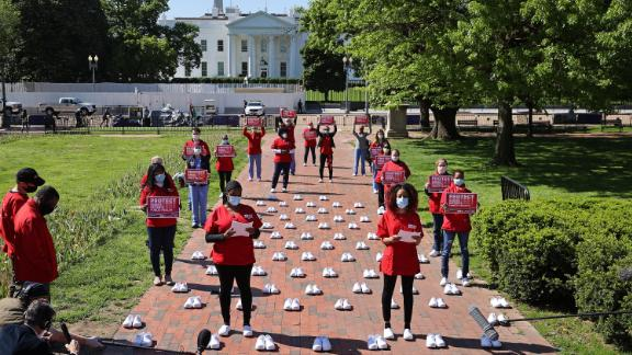 Members of the National Nurses United stand among 88 pairs of empty shoes representing nurses that they say have died from Covid-19 while demonstrating in Lafayette Park on May 7, 2020, across from the White House in Washington, DC.