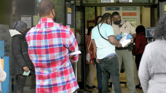 In this Thursday, April 23, 2020, photo a Pulaski County (Arkansas) Sheriff's officer gives out numbers as people wait in line at the Arkansas Workforce Center, in Little Rock. Payouts from the state's Unemployment Insurance Trust Fund soared last week to nearly $17.6 million.