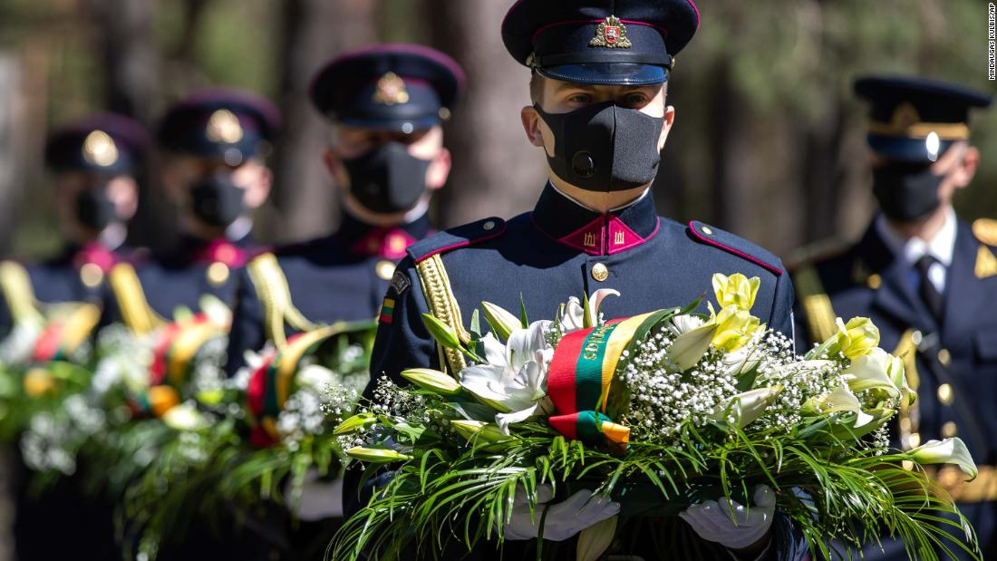 Soldiers wear protective face masks at a VE Day memorial in Vilnius, Lithuania, on Friday, May 8.