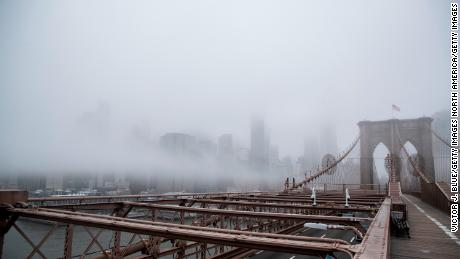 NEW YORK, NY - MARCH 20: Fog envelops the Manhattan skyline as the Brooklyn Bridge sits nearly empty of pedestrian traffic in the midst of the coronavirus (COVID-19) outbreak  on March 20, 2020 in New York City. The economic situation in the city continued to decline as New York Gov Andrew Cuomo ordered all nonessential businesses to keep all their workers at home and New York weighed a shelter in place order for the entire city. (Photo by Victor J. Blue/Getty Images)