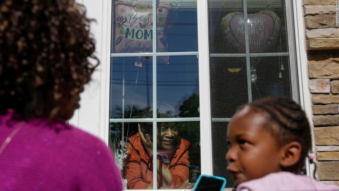 Mary Washington speaks through a window to her daughter Courtney Crosby and grandchild Sydney Crosby during a Mother's Day celebration at her senior-living facility in Smyrna.