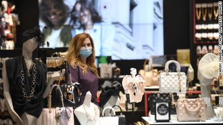 A vendor, wearing a mask for protection against the coronavirus, stands next to handbags at a shop in Dubai Mall.