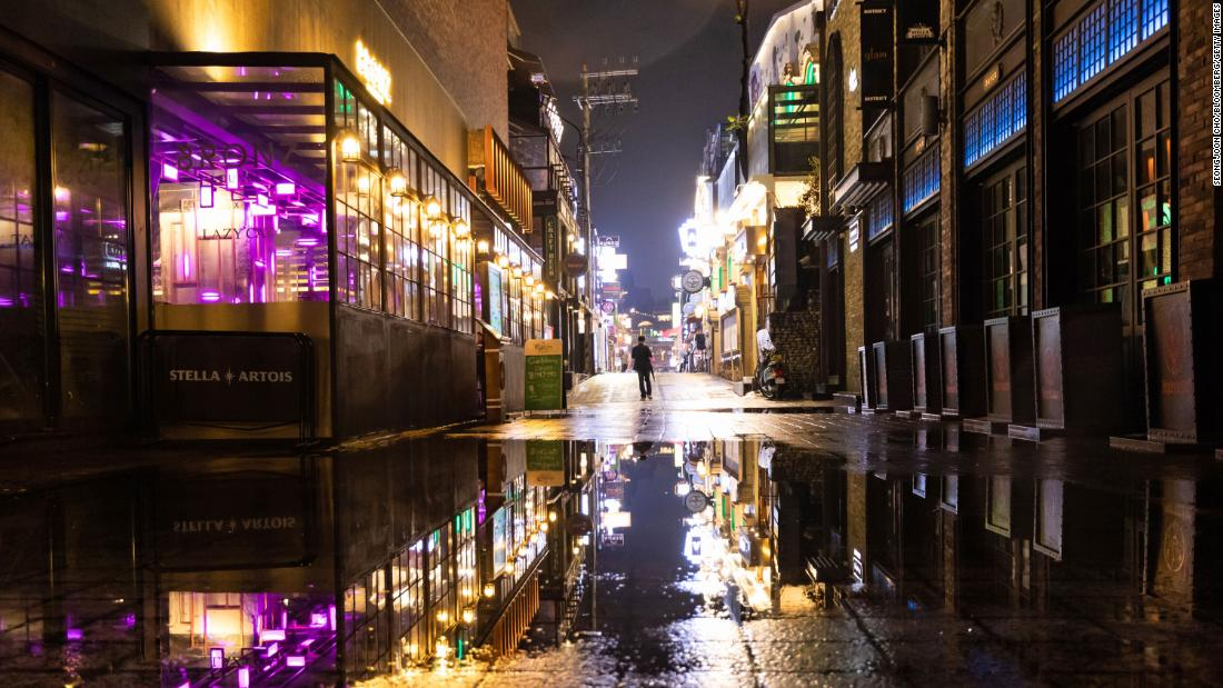 A person walks through the street at night in the Itaewon area of Seoul, South Korea, on Saturday, May 9, 2020.