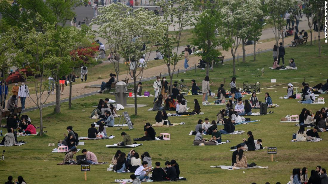 In a photo taken on May 10, 2020, people sit in a park in Seoul. - South Korea announced its highest number of new coronavirus cases for more than a month on May 11, driven by an infection cluster in a Seoul nightlife district just as the country loosens restrictions. (Photo by Ed JONES / AFP) (Photo by ED JONES/AFP via Getty Images)