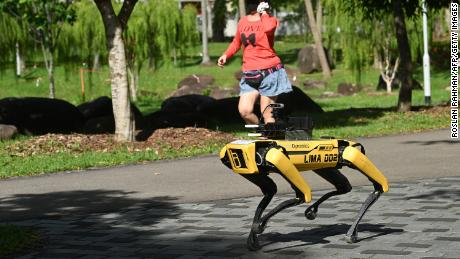TOPSHOT - A woman jogs past a four-legged robot called Spot, which broadcasts a recorded message reminding people to observe safe distancing as a preventive measure against the spread of the COVID-19 novel coronavirus, during its two-week trial at the Bishan-Ang Moh Kio Park in Singapore on May 8, 2020. (Photo by Roslan Rahman/AFP/Getty Images)
