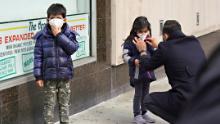 A man adjusts a child's protective mask amid the coronavirus pandemic.