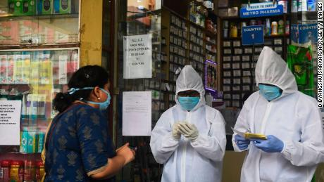 A pharmacy workers take an order of medicines from a customer outside the store as a preventive measure against the spread of the Covid-19 coronavirus in Kolkata on April 16, 2020.