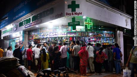 People gather at a pharmacy to buy supplies following Indian Prime Minister's announcement of a government-imposed nationwide lockdown as a preventive measure against the Covid-19 in Mumbai on March 24, 2020.