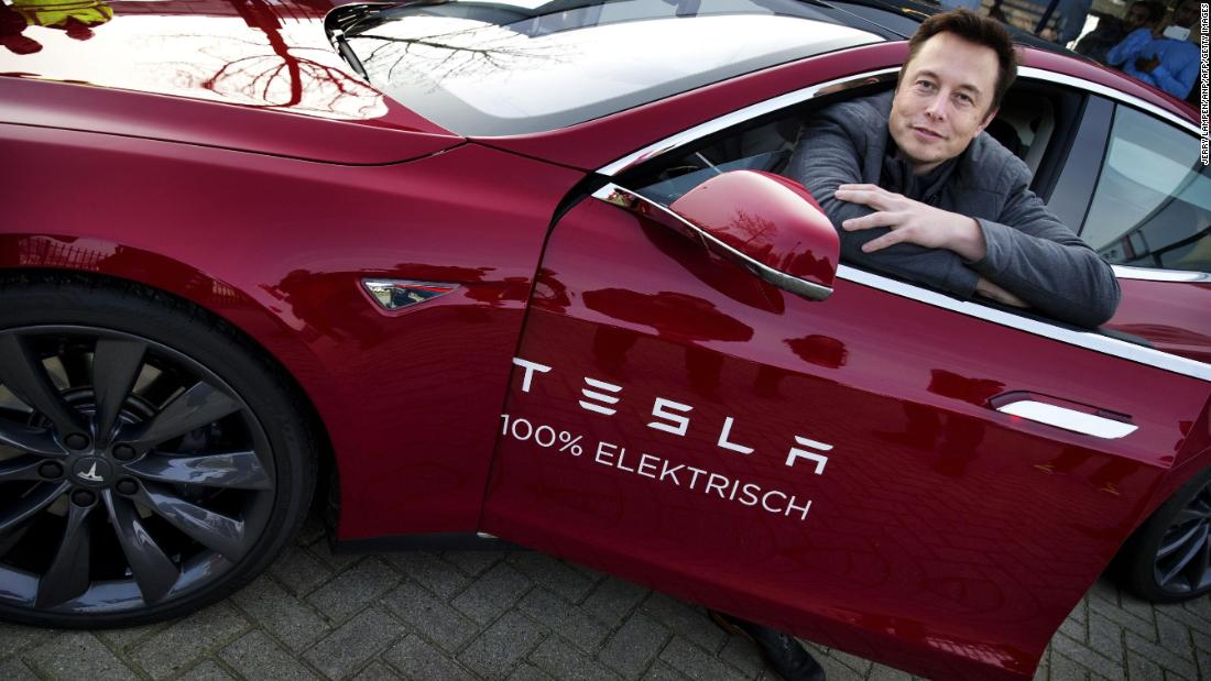 Musk poses with a Tesla during a visit to Amsterdam, Netherlands, in 2014.