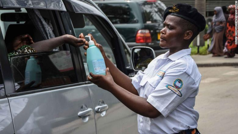 A security officer dispenses chlorinated water to a passenger at Muhimbili National Hospital in Dar es Salaam, Tanzania, a few hours after the government announces the first case of the Covid-19 in the country on March 16, 2020.