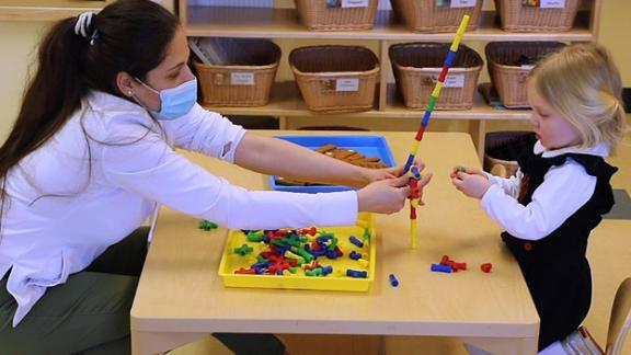 Preschool teacher Yafreisi Pepen is shown here with Keegan at Bright Horizons at Landmark in Boston. Bright Horizons has been running centers for essential workers in recent months.