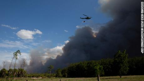 A helicopter carrying a bucket flies near a brush fire in Golden Gate Estates in Florida on Wednesday.