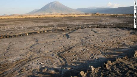 The Engare Sero footprint site is in Tanzania, which preserves at least 408 human footprints. An eruption of Oldoinyo L'engai, the volcano in the background, produced the ash in which the footprints were preserved, according to the researchers.