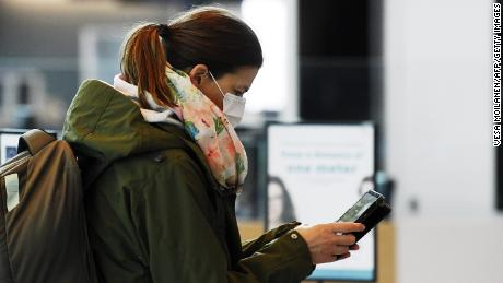 A passenger, wearing a face mask, looks at her phone at the Helsinki International Airport in Vantaa, Finland, on May 13, 2020. - The Finnish airport operator Finavia requires the use of mouth-nose protectors of all airport employees who work in the customer interface. It also strongly recommends that passengers use a mask as they move about the airport. (Photo by Vesa Moilanen/AFP/Getty Images)